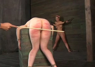 Depraved slavery master hits his slave's ass with a wooden stick