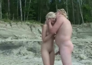 A pair of horny swingers on a nude lakeshore