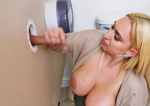A blonde is taking care of a cock through a glory hole