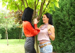Two tanned lesbian babes having a sexy vibrator session outdoors