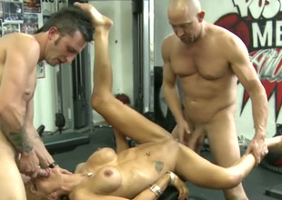 Blond haired super MILF works on two strong dicks in the gym