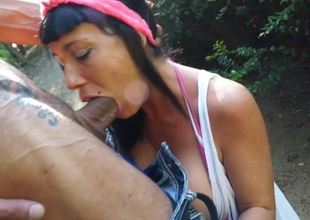 Busty playgirl sucks a cock in the park