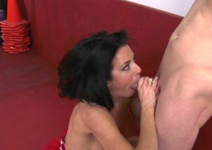 A milf that has large tits is licking a big dick in her uniform